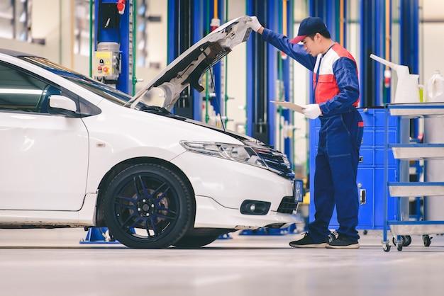 Um jovem mecânico de automóveis asiático em uma oficina de automóveis está analisando problemas no motor e verificando o motor