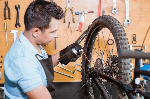 Um jovem mecânico usando luvas usando lubrificante de corrente para lubrificar a corrente e a roda livre