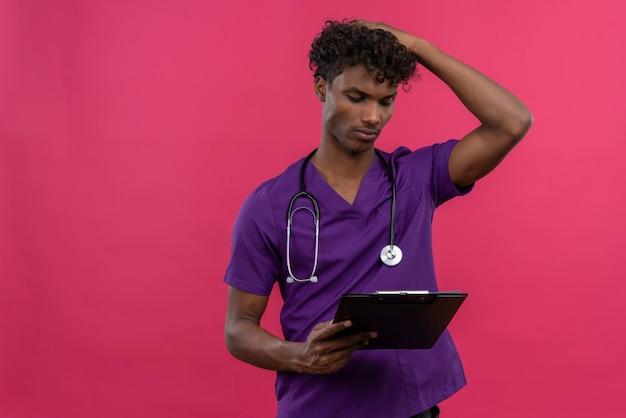 Um jovem médico bonito de pele escura com cabelo encaracolado e uniforme violeta com estetoscópio olhando para a prancheta mantendo as mãos na cabeça