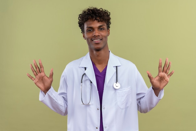 Um jovem médico bonito de pele escura com cabelo encaracolado, jaleco branco e estetoscópio sorrindo enquanto abre as mãos em um espaço verde