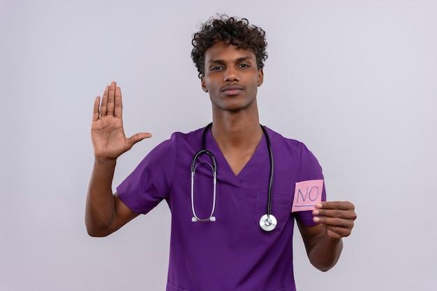 Um jovem médico bonito, de pele escura com cabelo encaracolado, usando uniforme violeta com estetoscópio mostrando um cartão de papel com a palavra não