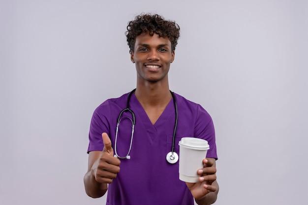 Um jovem médico bonito de pele escura com cabelo encaracolado, usando uniforme violeta com estetoscópio segurando um copo de papel de café com o polegar para cima