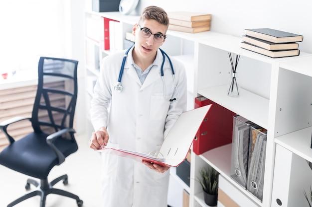 Um jovem médico com uma túnica branca em pé perto do rack e segurando uma pasta com documentos.