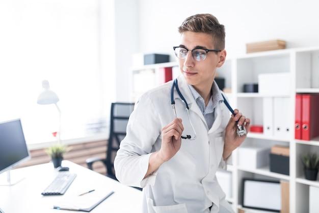 Um jovem médico em um manto branco está inclinado sobre a mesa no escritório ele tem um estetoscópio em volta do pescoço