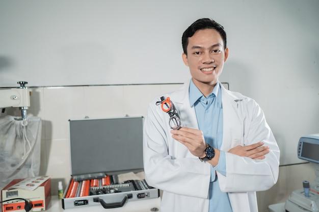 Um jovem médico posa segurando uma moldura de teste contra o pano de fundo de outro equipamento em uma clínica de olhos