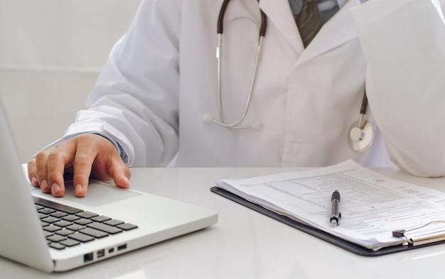 Um jovem médico preocupado com sua carreira médica no trabalho. com laptop notebook um terapeuta muito atencioso está preocupado em resolver problemas com drogas.
