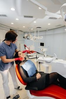 Um jovem médico trata os dentes do paciente. odontologia