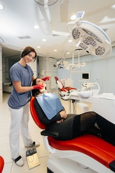 Um jovem médico trata os dentes do paciente. odontologia.