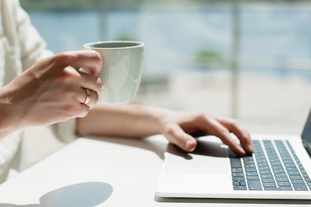 Um jovem millennial masculino trabalha remotamente em um laptop.