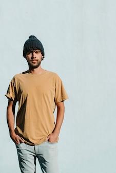 Um jovem modelo masculino bonito, posando com as mãos nos bolsos