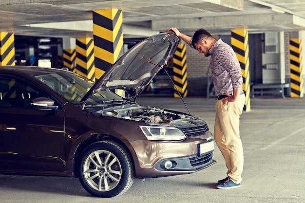 Um jovem motorista tenso e frustrado está ao lado de um carro quebrado e olha sob o capô no estacionamento.