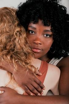 Um, jovem mulher africana, abraçando, loiro, mulher jovem, olhando câmera