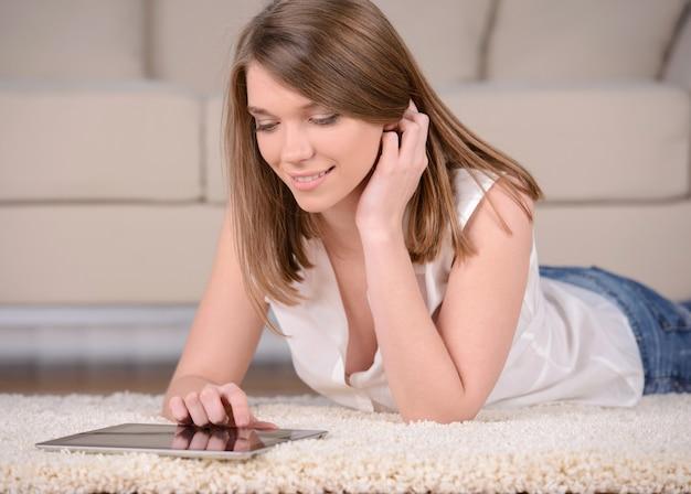 Um, jovem, mulher sorridente, sentando, ligado, um, sofá, é, segurando, um, tablete