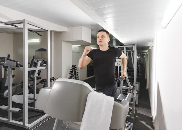 Um jovem na academia fazendo exercícios em uma esteira. treino intensivo do clube de fitness