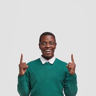 Um jovem negro encantado e sorridente levanta dois dedos da frente, tem uma expressão facial alegre, mostra um espaço livre acima da cabeça