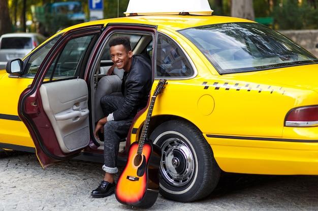 Um jovem no carro com a porta aberta
