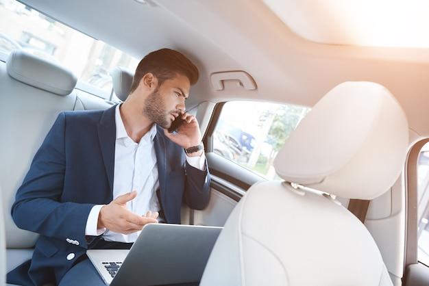 Um jovem no carro discutindo assuntos de negócios ao telefone