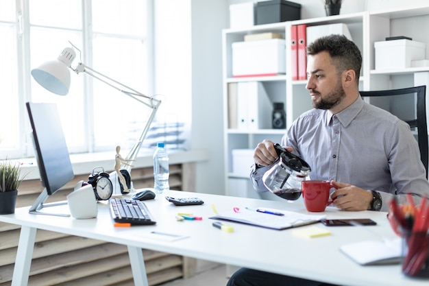 Um jovem no escritório se senta à mesa, olha para o monitor e serve café em uma xícara.