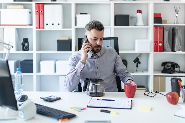 Um jovem no escritório se senta em uma mesa, falando ao telefone e segurando um copo vermelho na mão.