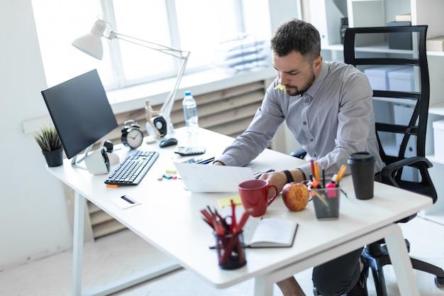Um jovem no escritório senta-se a uma mesa, segura uma tampa do marcador na boca e trabalha com documentos.
