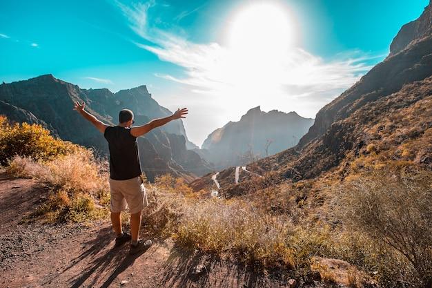 Um jovem olhando para a paisagem do monte masca, na ilha de tenerife, nas ilhas canárias. espanha