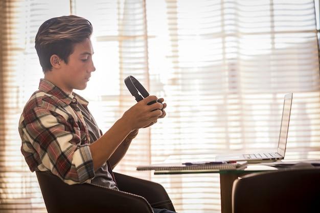 Um jovem ou adolescente estudando e fazendo lição de casa com o laptop em casa sozinho. millennial seguindo aulas online da escola para o bloqueio. belo homem usando computador e dispositivo de tecnologia