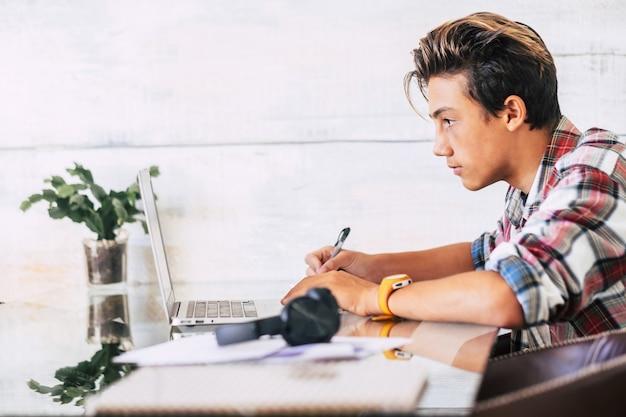 Um jovem ou adolescente estudando e fazendo lição de casa com um laptop sozinho em casa