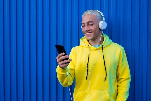 Um jovem ouvindo e ouvindo música, sorrindo e olhando para o telefone se divertindo - uma parede azul colorida ao fundo - amando o conceito de música e usando tecnologia de estilo de vida