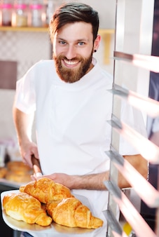 Um jovem padeiro masculino bonito segura uma bandeja com croissants franceses na frente de uma padaria e sorri.