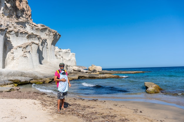 Um jovem pai caminhando com seu filho pela praia do enmedio, em cabo de gata, em um lindo dia de verão, almería