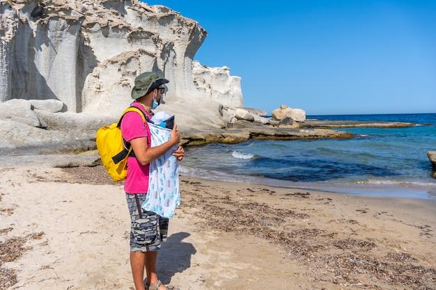 Um jovem pai caminhando com seu filho pela praia do enmedio, em cabo de gata, em um lindo dia de verão, almeria