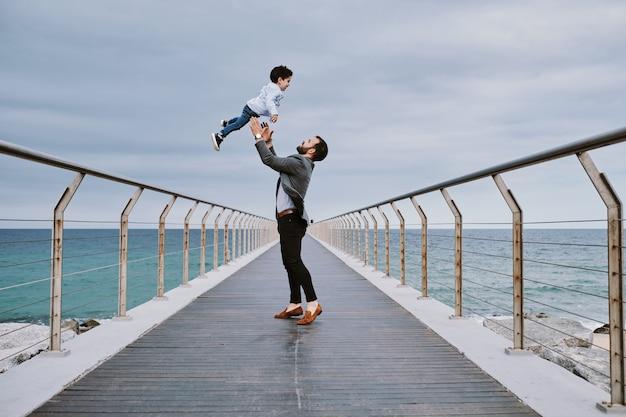 Um jovem pai em uma ponte com seu filho voando em cima dele