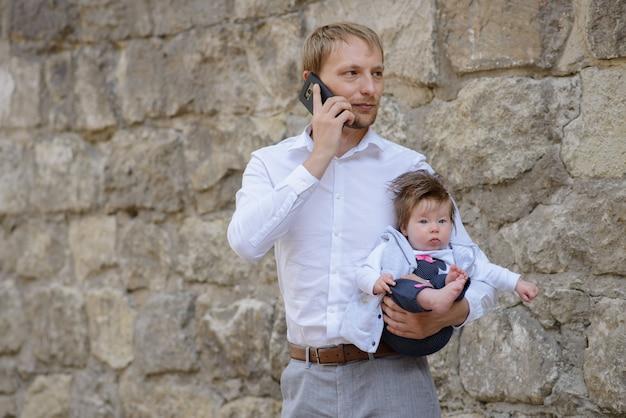 Um jovem pai está falando no celular e segura a filha nos braços. copie o espaço