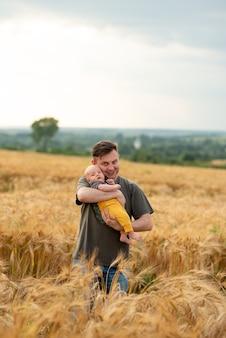 Um jovem pai segura seu filho de três meses nos braços.