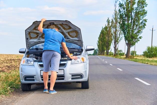 Um jovem perto do carro com um capô aberto ao lado da estrada.