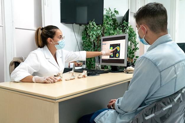 Um jovem podólogo mascarado explicando o diagnóstico a um paciente