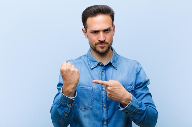 Um jovem posando enquanto olha impaciente e com raiva, apontando para o relógio