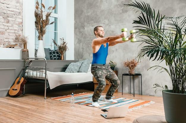 Um jovem pratica esportes em casa, faz exercícios on-line no laptop