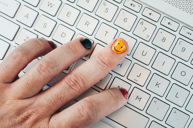Um jovem programador trabalha em um computador. close-up de unhas pintadas. unhas pintadas na moda na mão de um homem. manicure masculina