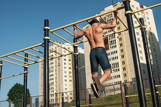 Um jovem puxa-se para cima no campo de esportes, um atleta