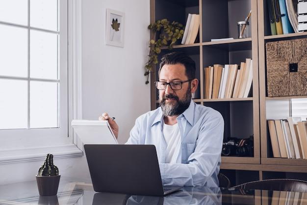 Um jovem que trabalha em casa no escritório com laptop e notebook tomando notas falando em uma videoconferência. um empresário ligando para se comunicar