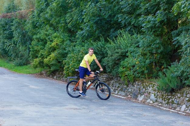 Um jovem rapaz anda de bicicleta ao ar livre