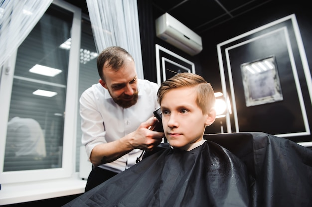 Um jovem rapaz bonito cortando o cabelo
