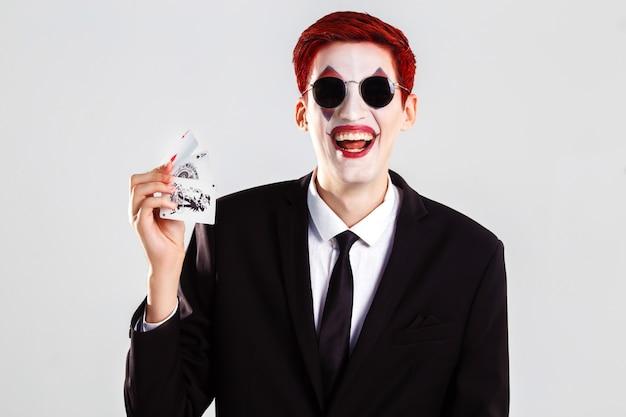 Um jovem rapaz com um coringa de maquiagem artística. conceito de jogo e cassino. foto de estúdio. fundo branco .