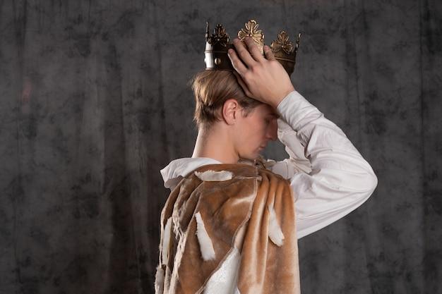 Um jovem rei em um manto de pele coroa a si mesmo, um homem segura uma coroa sobre sua cabeça. um personagem de fantasia histórica ocupa o trono. foto no estúdio no perfil lateral, em fundo cinza