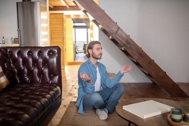 Um jovem relaxado meditando em seu apartamento