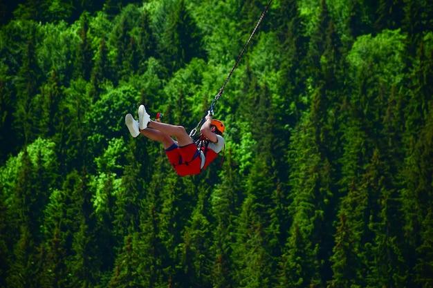 Um jovem saltou de bungee jumping e agora se pendura em uma corda e se filma em uma câmera de vídeo esportiva contra um fundo desfocado de uma floresta verde