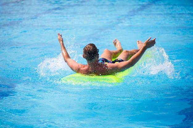 Um jovem se banha na piscina em um colchão inflável amarelo. relaxe sob o sol forte nas férias. feliz cara de sucesso. foco seletivo