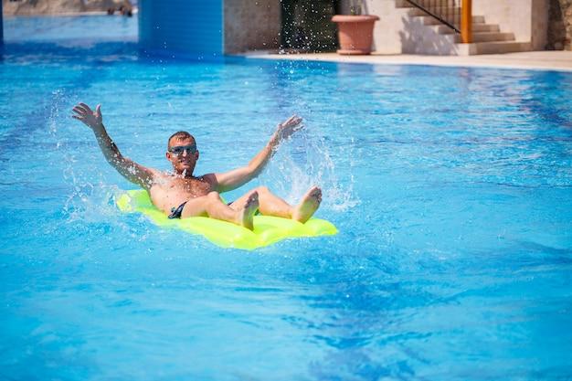 Um jovem se banha na piscina em um colchão inflável amarelo