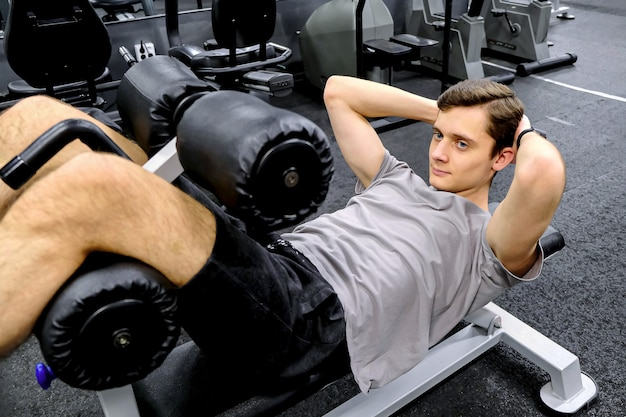 Um jovem se exercita no simulador na academia. treina a força muscular. o conceito de estilo de vida saudável.